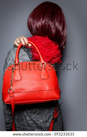 Woman dressed in spring or fall fashion holding a red purse or bag - stock photo
