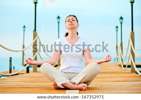 woman dressed in white doing yoga on the pier near the sea - stock photo