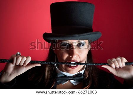 Woman dressed like a circus ringmaster with whip