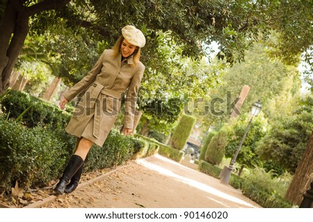 woman dressed with coat and beret walking on an edge - stock photo