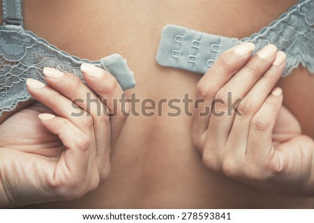 Woman dressing brassiere. Close-up rear view photo - stock photo