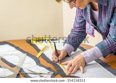 Woman dressmaker drawing tailor pattern with pencil for a suit on the table - stock photo