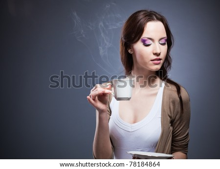 Woman drifting off into a land of coffee fantasy, as she smells the fresh brew with her eyes closed. - stock photo