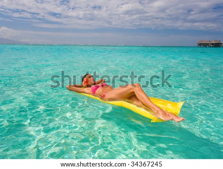 woman drifting on yellow raft in turquoise waters