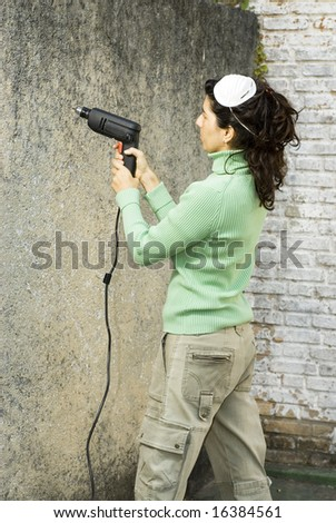Woman drills hole in wall. She is wearing a dust mask on her head. Vertically framed photo. - stock photo