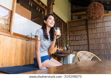 Woman drink of the coffee and sitting on chair - stock photo