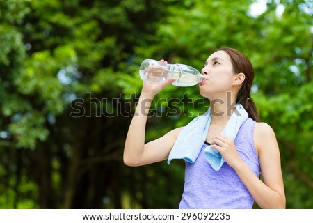 Woman drink of the water with running tracksuit - stock photo