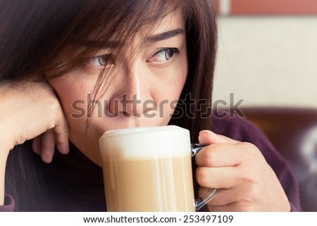 woman drinking a coffee latte in cafe - stock photo