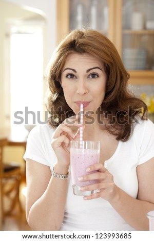 Woman drinking a fruit smoothie through a straw in kitchen setting looking at camera - stock photo