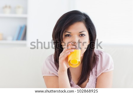 Woman drinking a glass of orange juice in a living room - stock photo