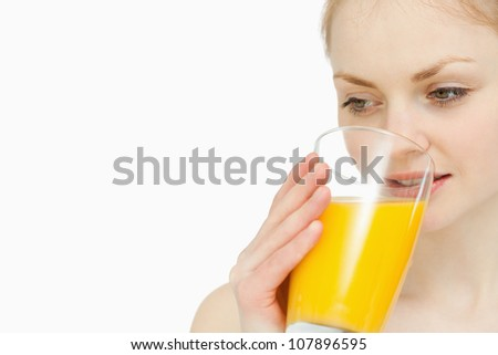 Woman drinking a glass of orange juice while looking away against white background - stock photo