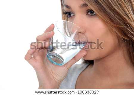 Woman drinking a glass of water - stock photo