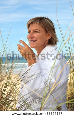 Woman drinking a glass of water on a sand dune - stock photo