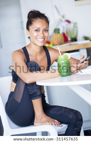 Woman drinking a homemade green detox juice, wearing sportive clothing. - stock photo