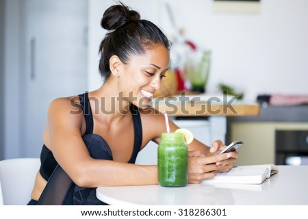 Woman drinking a homemade green detox juice, wearing sportive clothing, texting on her  phone while sitting in her kitchen table - stock photo