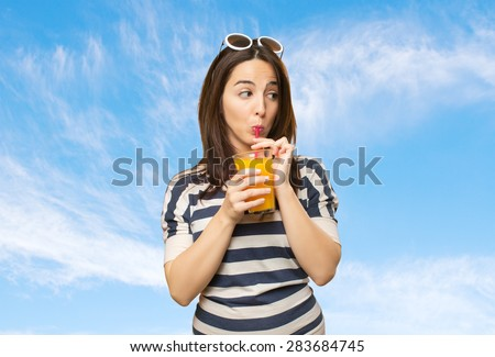 Woman drinking a juice with a red straw. Over clouds background. Over clouds background - stock photo