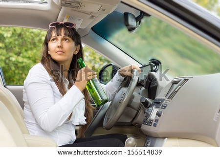 Woman drinking alcohol from a bottle behind the wheel of her car and turning to look up through the open sunroof - stock photo
