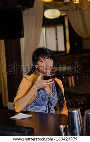 Woman drinking alone at the bar sitting at the counter holding a large glass of red wine in her hand as she looks at the camera with a thoughtful expression - stock photo