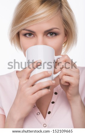 Woman drinking. Attractive young blond hair woman drinking something from cup and looking at camera while isolated on white - stock photo