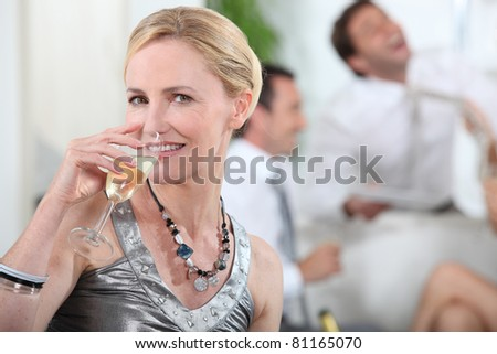 Woman drinking champagne at a party - stock photo