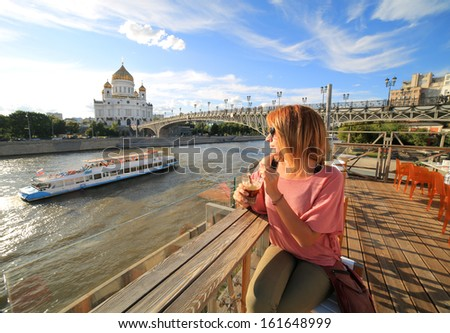 woman drinking cocktail at a club, moskow view on background with Cathedral of Christ the Saviour, Moskva River and daily city life - stock photo