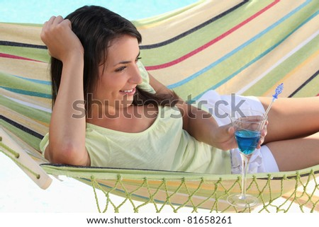 Woman drinking cocktail whilst lying on hammock - stock photo