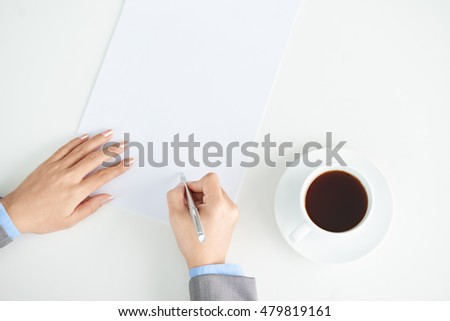 Woman drinking coffee and writing ideas, view from above