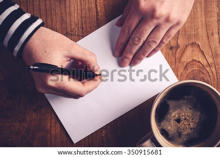 Woman drinking coffee and writing letters, top view of female hands writing recipient address on white envelope, retro toned image with selective focus. - stock photo