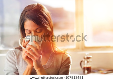 Woman drinking coffee at home with sunrise streaming in through window and creating flare into the lens. - stock photo