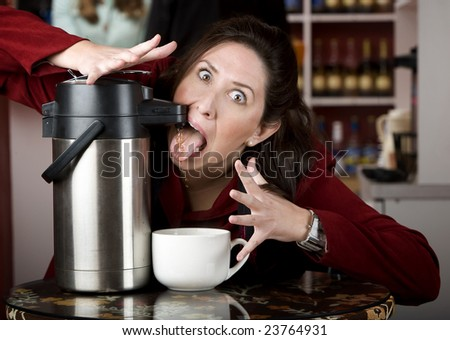 Woman drinking coffee directly from a beverage dispenser - stock photo