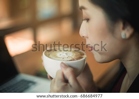 Woman drinking coffee in a cafe. Portrait of happy brunette with mug in hands.
