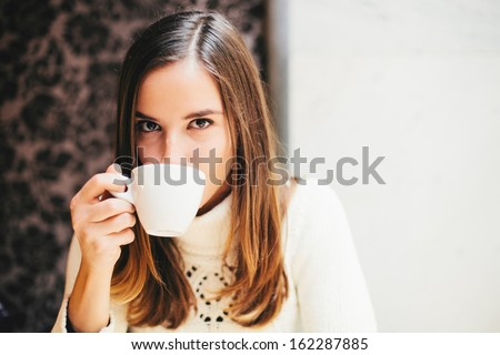 Woman drinking coffee in cafe - stock photo