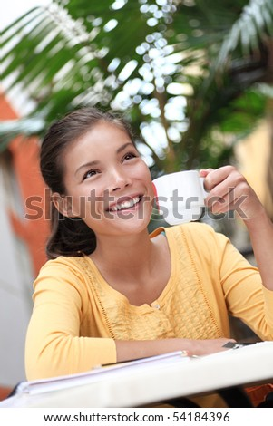 Woman drinking coffee in cafe outside. Asian woman enjoying coffee on cafe terrace outdoors in the summer time.
