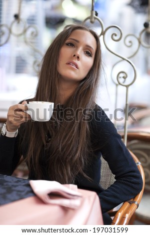 Woman drinking coffee in coffee shop and waiting for her boyfriend - stock photo