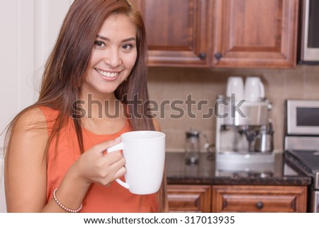 Woman drinking coffee in her nice kitchen - stock photo