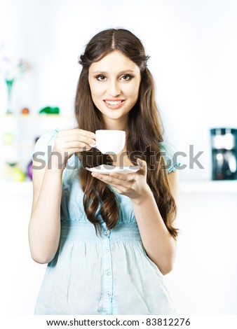 woman drinking coffee in the kitchen - stock photo