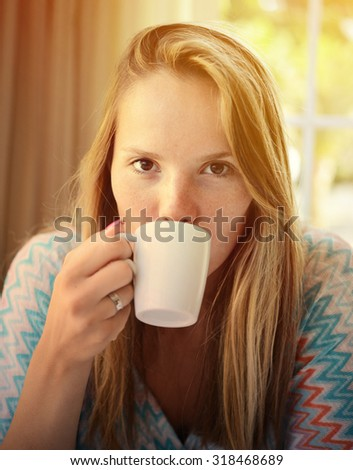 Woman drinking coffee in the morning at restaurant - stock photo