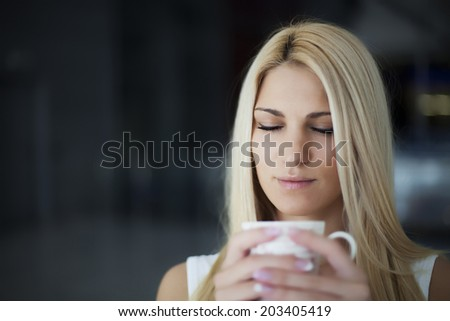woman drinking coffee in the morning eyes closed ( small depth of field, focus on closed eyes)  - stock photo
