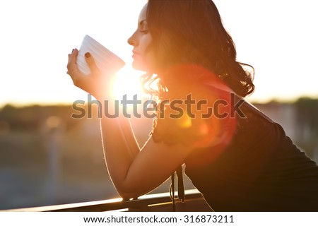 Woman drinking coffee in the sun, outdoor in sunlight light, enjoying her morning coffee. - stock photo