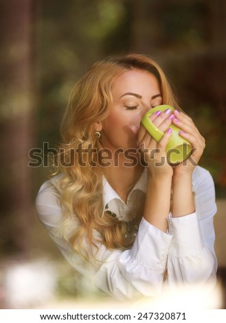 Woman drinking coffee indoors, enjoying the aroma of beverage, view through the window - stock photo