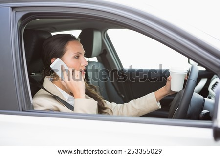 Woman drinking coffee on phone while driving in her car - stock photo