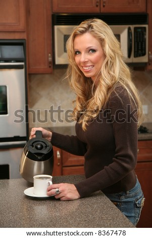 Woman drinking coffee standing in her luxury kitchen - stock photo