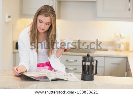 Woman drinking coffee while reading the newspaper in kitchen