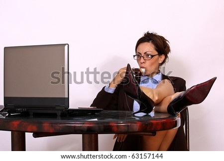 Woman drinking coffee while working on lap top computer