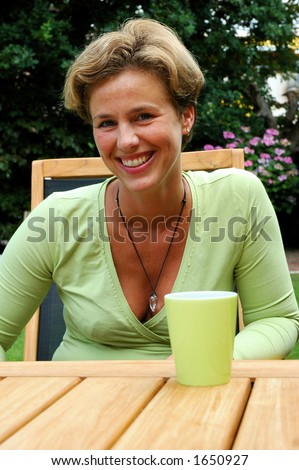 Woman drinking cup of coffee in the garden