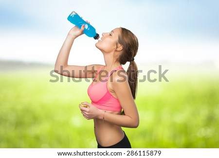 Woman drinking from a blue bottle. Over nature background - stock photo