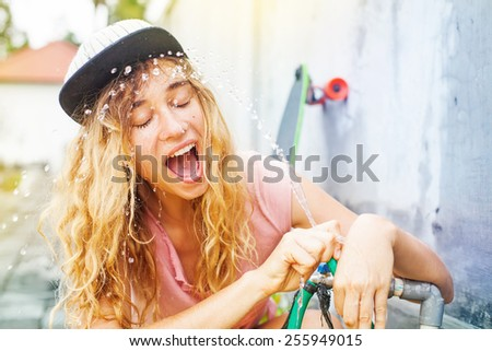 woman drinking from a hose after skating - stock photo