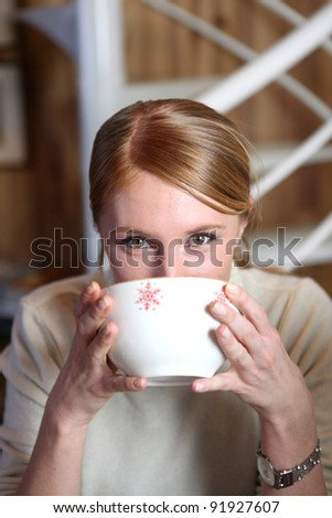 Woman drinking from coffee bowl - stock photo