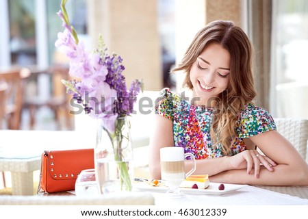 Woman drinking hot latte coffee and eating cake at cafe. Summer time