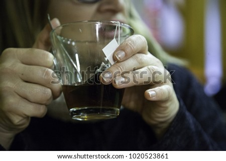 Woman drinking infusion in bar, relaxing drink, and herbs